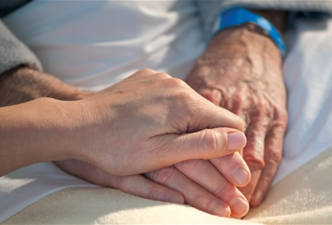 Someone holding a senior's hand