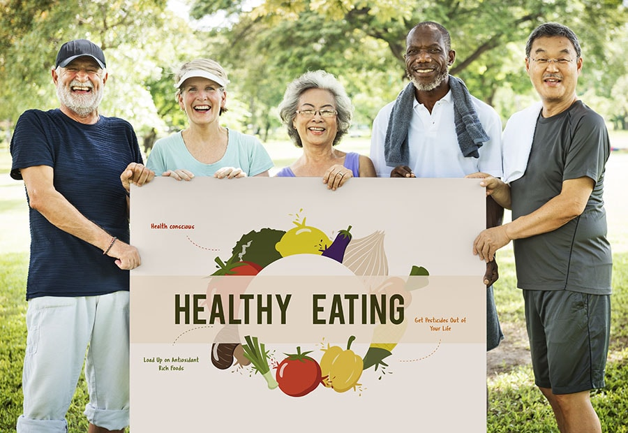 "Group of smiling seniors holding a sign that reads ""Healthy Eating"""